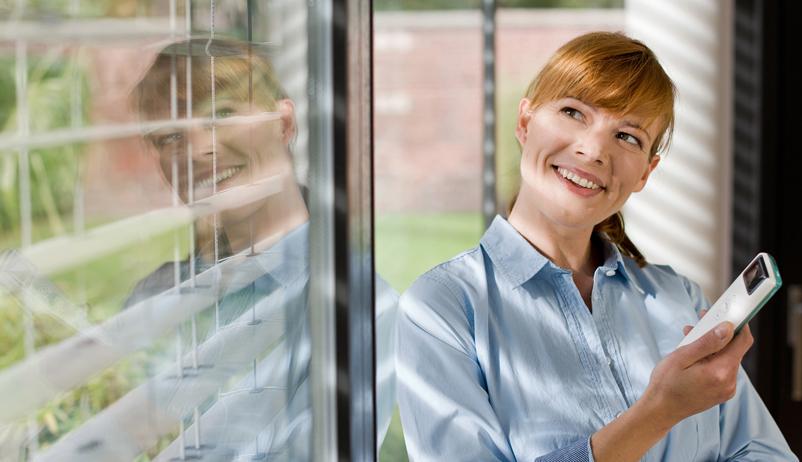 Junge Frau mit Fernbedienung in der Hand vor offenem Rollladen